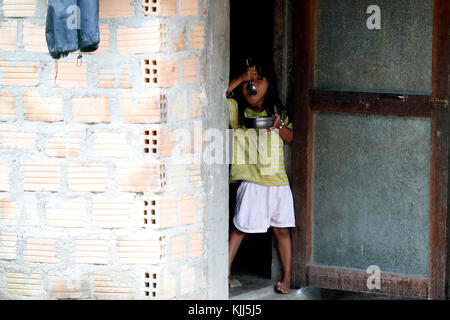 Bahnar (Ba Na) ethnic group.  Young girl eating.  Kon Tum. Vietnam. - Stock Photo