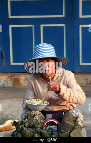 Vietnamese woman eating soup with chopsticks.  Hoi An. Vietnam. - Stock Photo