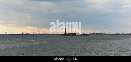 View of the Statue of Liberty over the water with cargo crains in the distance. - Stock Photo