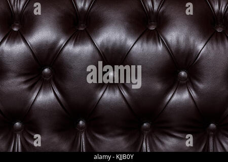 Closeup shot of dark brown leather texture with buttons. Furniture texture - Stock Photo