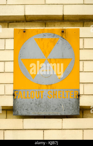 Atomic nuclear fallout shelter sign with radiation symbol on a brick wall. - Stock Photo