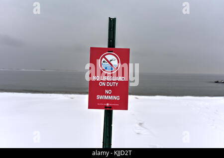 Winter snow on the beach. Sign clearly stating, No Swimming. - Stock Photo