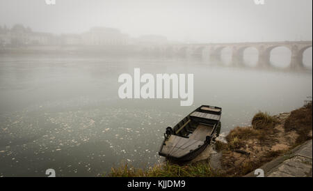 'Toue' fishing boat anchored on the Loire river in front of a misty city view of Saumur, with bridge - Stock Photo