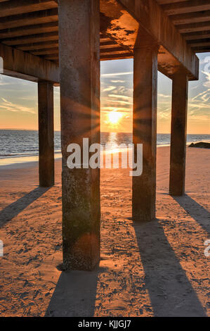 Coney Island Beach at sunset with a vivid, dramatic sky and long shadows. - Stock Photo