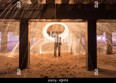 Showers of hot glowing sparks from spinning steel wool at Coney Island Beach, Brooklyn, New York. - Stock Photo