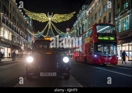 LONDON - NOVEMBER 21, 2017: Double decker buses and black cabs jam the streets under twinkling Christmas angels - Stock Photo
