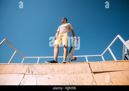 Young man with longboard on top of halfpipe in skatepark - Stock Photo