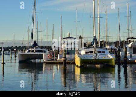 Sailing catamarans and large power boats berthed in marina. - Stock Photo