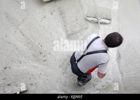 Construction site. Worker pouring concrete.  France. - Stock Photo