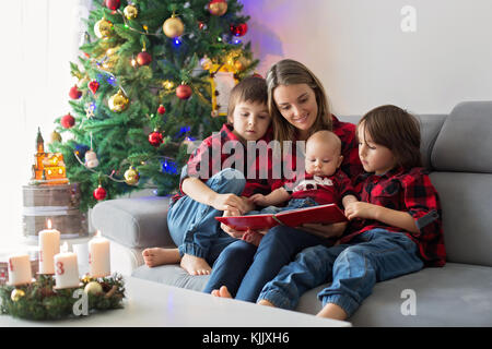 Happy family portrait on Christmas, mother, reading a book to her three children sitting on couch at home, chritmas - Stock Photo