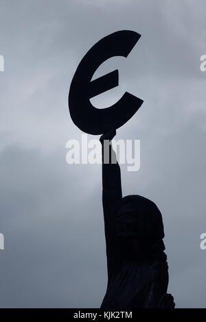 A Bronze statue of the goddess Europa holding a euro symbol under a cloudy sky outside the European Parliament building - Stock Photo
