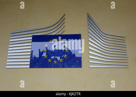 A sign featuring the EU logo on the European Commission building, with EU flags reflected in it, in the Belgian - Stock Photo