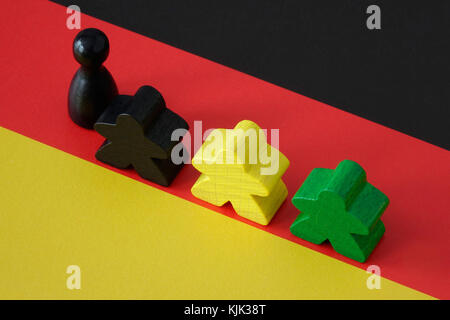 24.10.2017, Board game pieces in the Jamaican national colours on a German flag. The next German government could - Stock Photo
