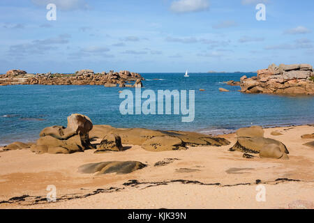 A sailing boat on the sea behind rock formations on the pink granite coast, in Tregastel (France) in Brittany, 03.10.2017. - Stock Photo