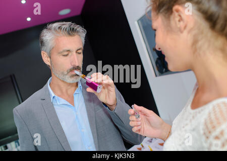 handsome mature man trying electronic cigarette at shop - Stock Photo
