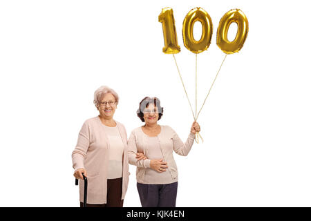 Two mature women with a number hundred balloon isolated on white background - Stock Photo