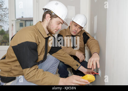 builders using a yellow multimeter to calibrate house - Stock Photo