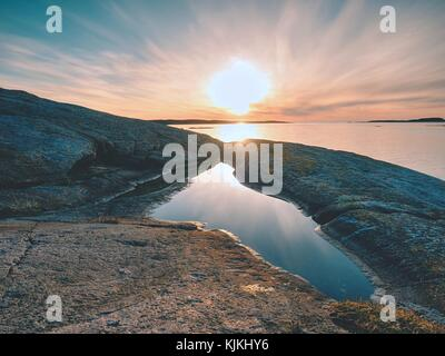 Concept of seascape sunset or sunrise background with rich reflection in water pool. The sun is hanging at horizon - Stock Photo
