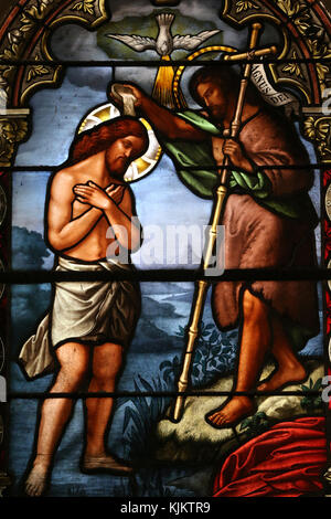 Jesus' baptism in the river Jordan by Saint John the Baptist. Stained glass window. Saint Vincent church.  Nyons. - Stock Photo