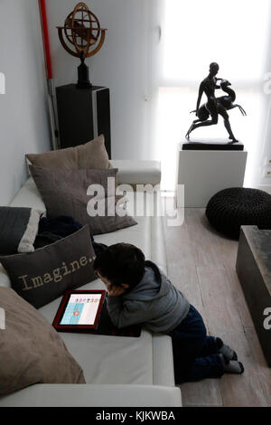 Little boy playing with a digital tablet on a couch. Marseilles. France. - Stock Photo