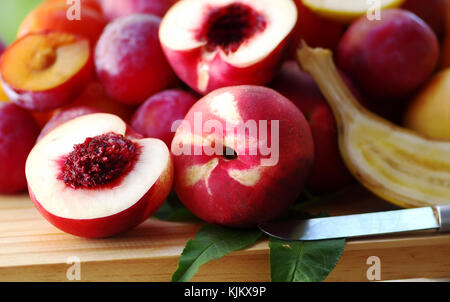 ripe peaches, nectarines and plums on table - Stock Photo