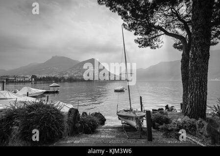 Boats and trees on Lake Lugano, mountain Monte Bre in the background. Black and white photography. - Stock Photo