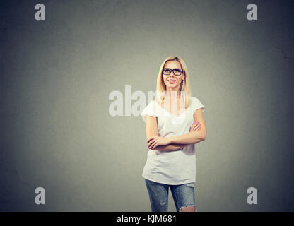 Portrait of happy woman thinking looking up while standing near a concrete wall. - Stock Photo