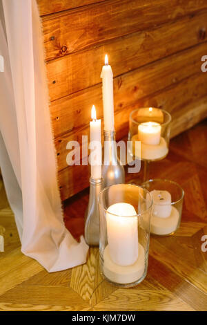 handmade, decor, cosiness concept. on the floorboards there are different design candle holders, few of them are - Stock Photo