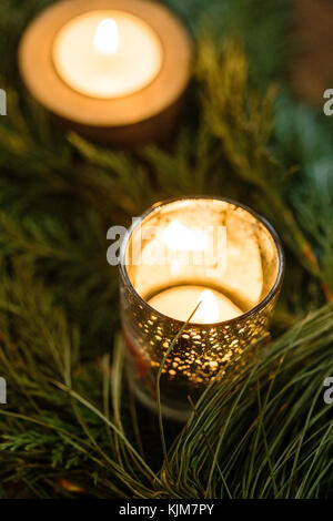nature, winter, decor concept. close up of small burning candles in different holders with silver dots, that shine - Stock Photo