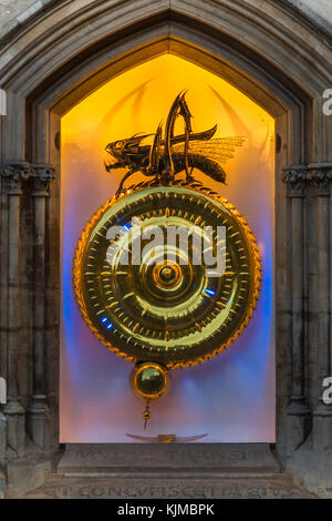 The Corpus Christi Clock with the Chronophage (or Time Eater)  illuminated at dusk, Kings Parade, Cambridge, England, - Stock Photo
