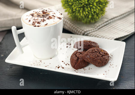 ustic cookies with cocoa and pistachios on white tray, ceramic foam cup with cappuccino and cocoa powder, cloth - Stock Photo