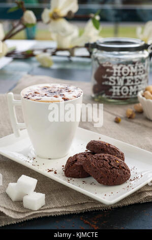 rustic cookies with cocoa and pistachios on white tray, ceramic foam cup with cappuccino and cocoa powder, sugar - Stock Photo
