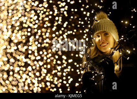 Dannielle McAllister looks through a beech hedge covered in fairy lights which is one of a series of light installations - Stock Photo