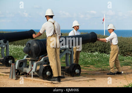 Firing of artillery cannon by tour guides dressed in British army military style clothes; a demonstration for tourists. - Stock Photo