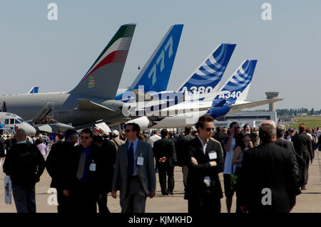 Boeing 767 tanker, Boeing 777-240LR, Airbus A380-800 and Airbus A340-600 tails in static-display with people walking - Stock Photo