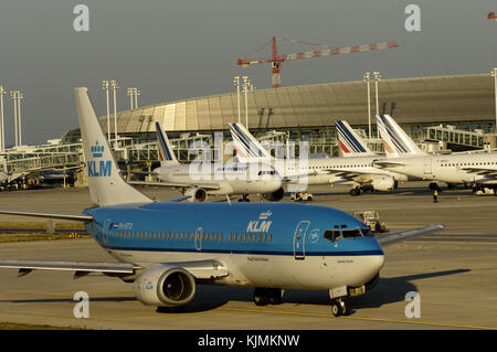 KLM taxiing on a taxiway with Air France airliners parked at Terminal2 and construction cranes behind - Stock Photo