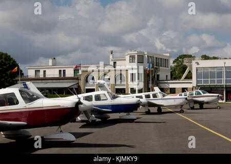 row of light-aircraft, Piper Cherokees and a Beech Bonanza parked on apron with terminal behind - Stock Photo