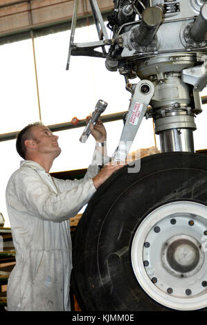 engineer inspecting nose wheel undercarriage with a flash light torch in the BASCO hangar - Stock Photo