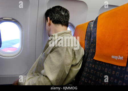man looking out of the window in his economy-class cabin seat BRS-GVA - Stock Photo