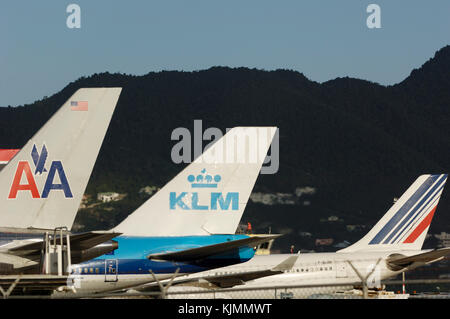 Airliners tail fins, an American Airlines B757, KLM B747 and Air France A340 in a row, on the ground, at Sint Maarten - Stock Photo