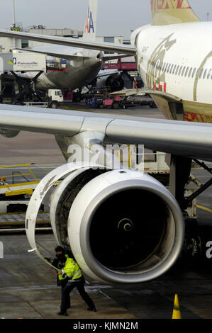 a Rolls-Royce Trent 772B-60 engine on a Gulf Air Airbus A330-200 being inspected by men wearing yellow high-viz - Stock Photo