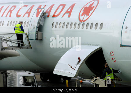 Men wearing yellow high-viz tabards loading cargo and catering into an Air Canada Airbus A340-300 parked at Terminal3 - Stock Photo