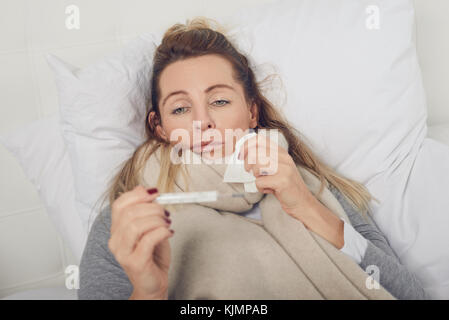 Sick woman with a miserable expression taking her temperature as she lies in bed suffering from a seasonal cold - Stock Photo