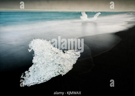 Lumps of ice at Diamond Beach in Iceland. - Stock Photo