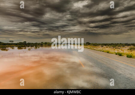 Water running over Great Northern Highway after heavy rain in Western Australia's outback. - Stock Photo