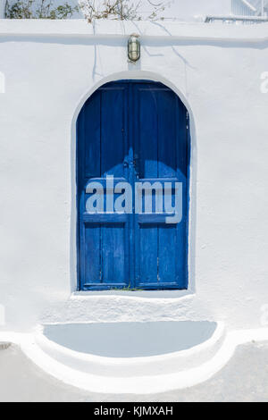 Traditional Greek architecture, a blue painted doorway with whitewashed walls. Taken on the island of Santorini. - Stock Photo
