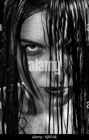 serious angry woman with wet black hair looking at camera, monochrome - Stock Photo
