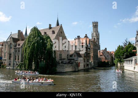 Cityscape of Bruges, Flanders, Belgium. Water canal at Rozenhoedkaai with old brick buildings and Belfry Tower on - Stock Photo