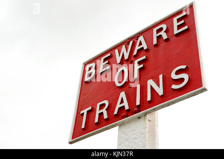 Low angle view of an old style BEWARE OF THE TRAINS sign - Stock Photo
