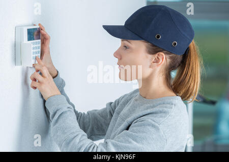 female electrician installing security system - Stock Photo